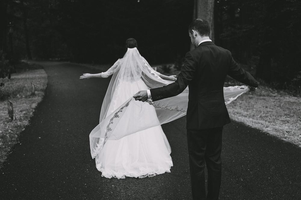 zwart wit trouwfoto met lange bruidssluier